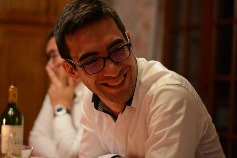 Rémy Vuong, en lunettes et chemise blanche, regarde hors champ, arborant un grand sourire.